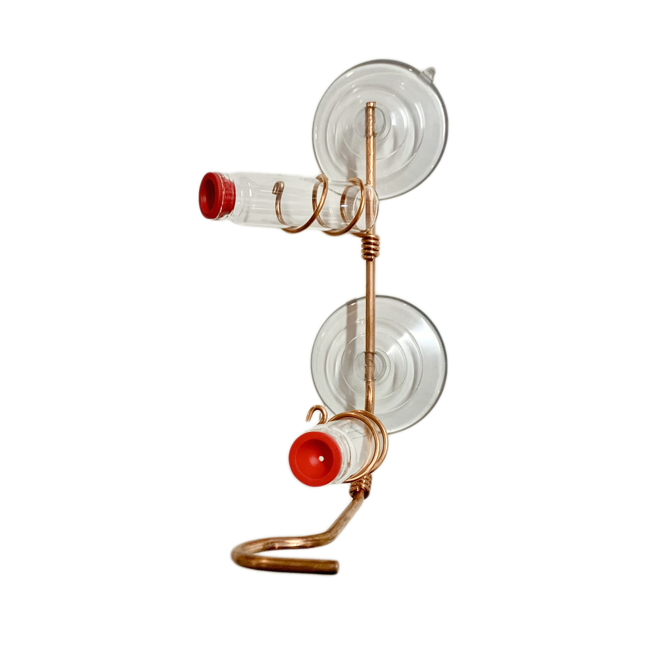 A simple window hummingbird feeder made from copper wire and two glass vials stands out on a white background