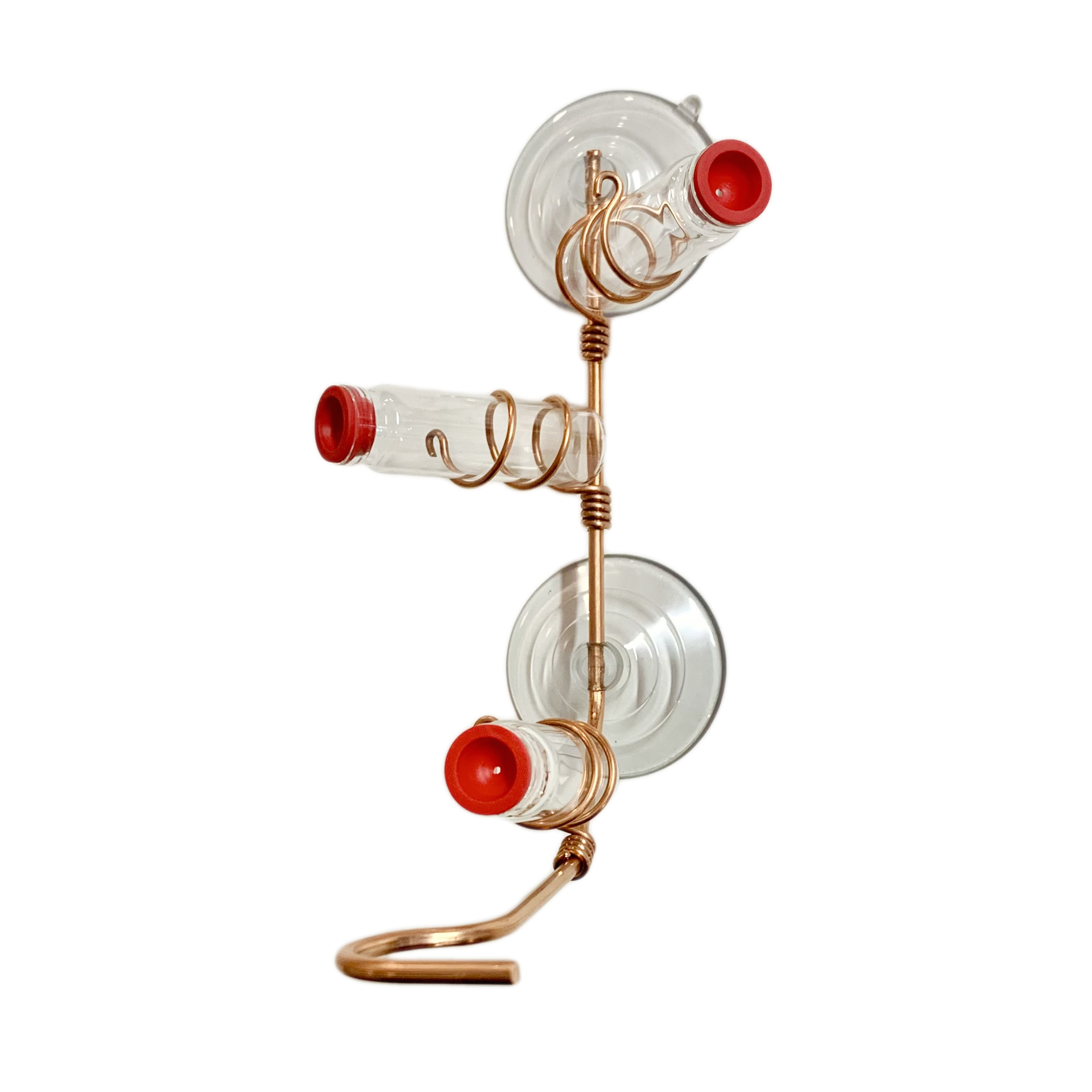 A simple window hummingbird feeder made from copper wire and three glass vials stands out on a white background